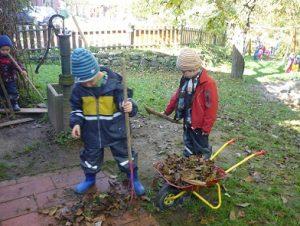 Kinder beim Laubharken